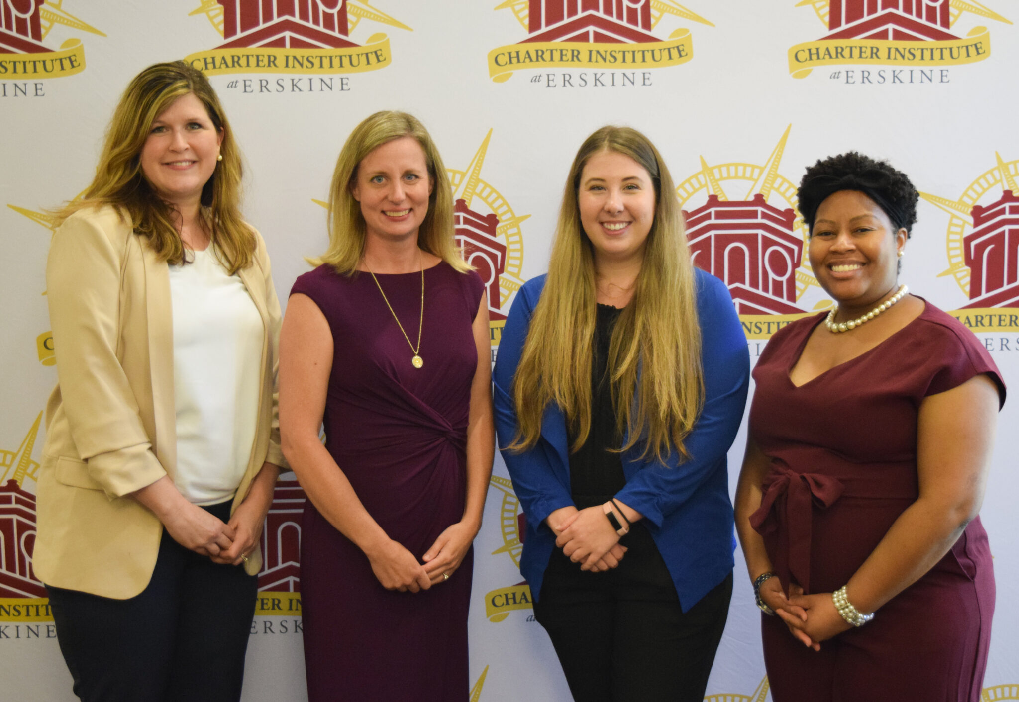 Four women in business attire in front of the Erskine Charter backdrop.